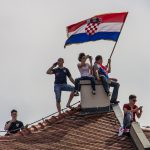 Group of people perched on a rooftop with a Croatian flag