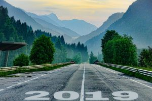 "Road leading to a forest and mountains with ""2019"" printed on it"